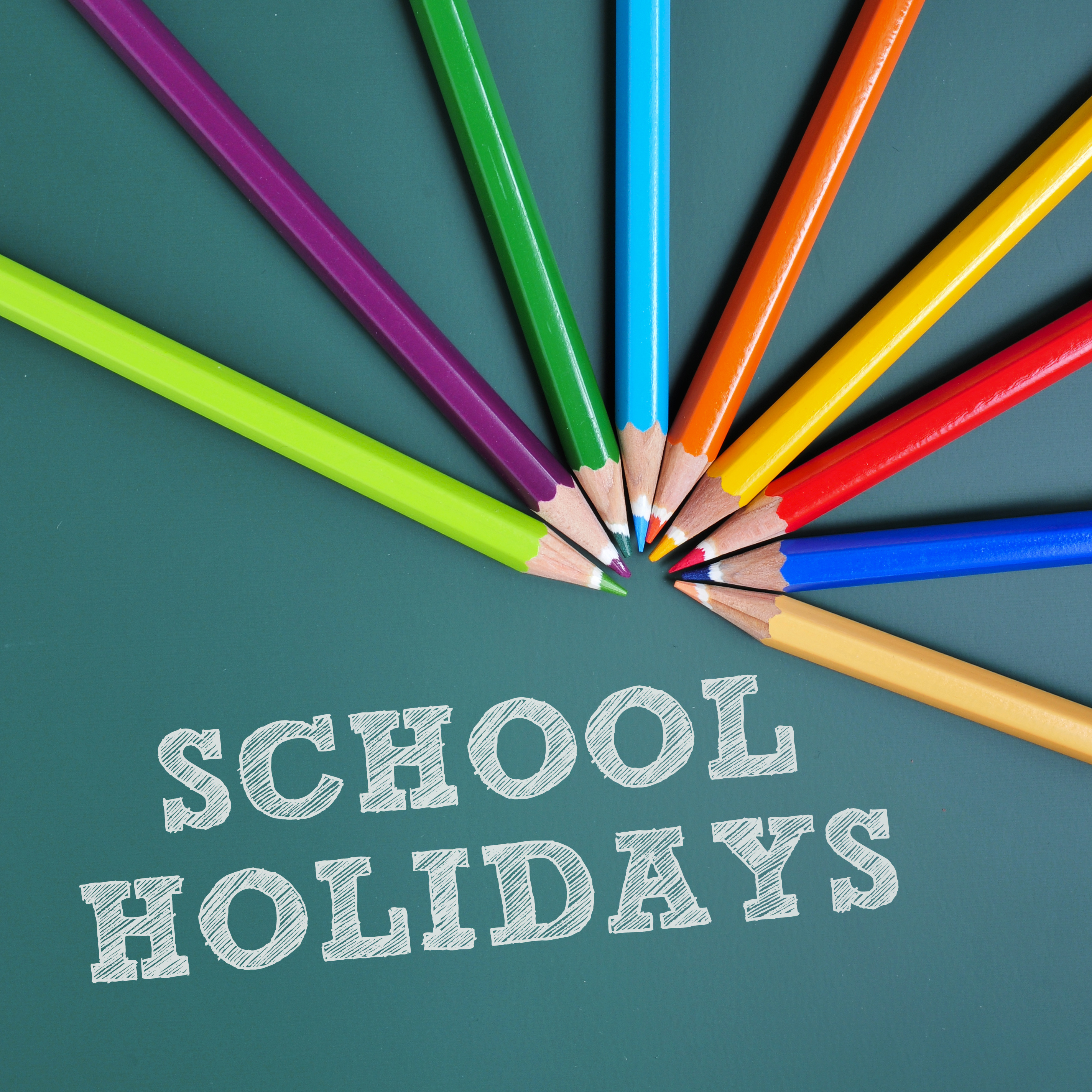 School holidays sign with circle of coloured pencils